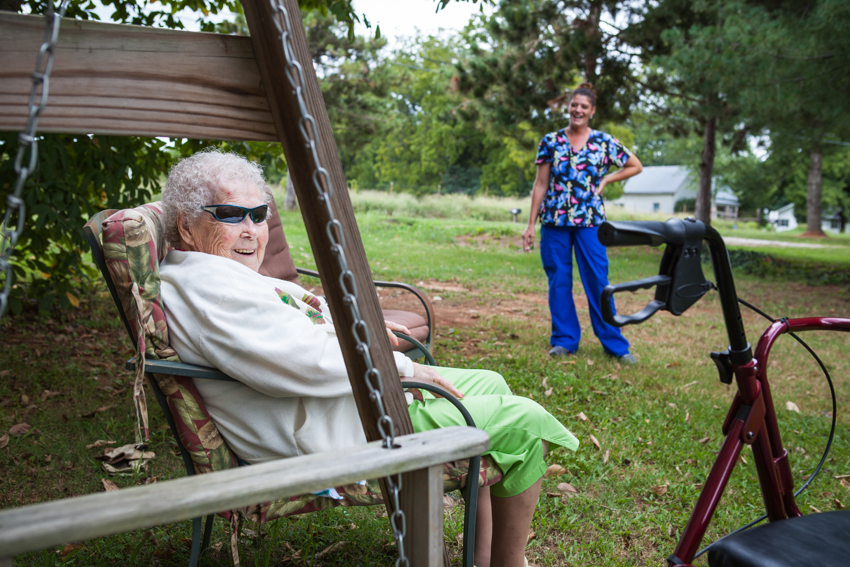 Elderly woman on a swing, wearing funny sunglasses, with her caregiver nearby. Smiling, laughing, happy, healthcare, aid, worker, work, at work, costs, medical, physical therapy, disability, rehabilitation, aging