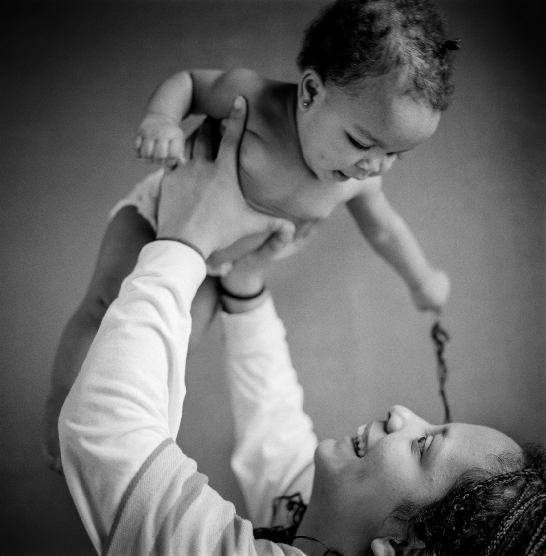Young mother holding her daughter. Mother playing with her baby.  Nashville, Chicago, Washington, DC documentary and editorial portrait photographer photojournalist Kristina Krug