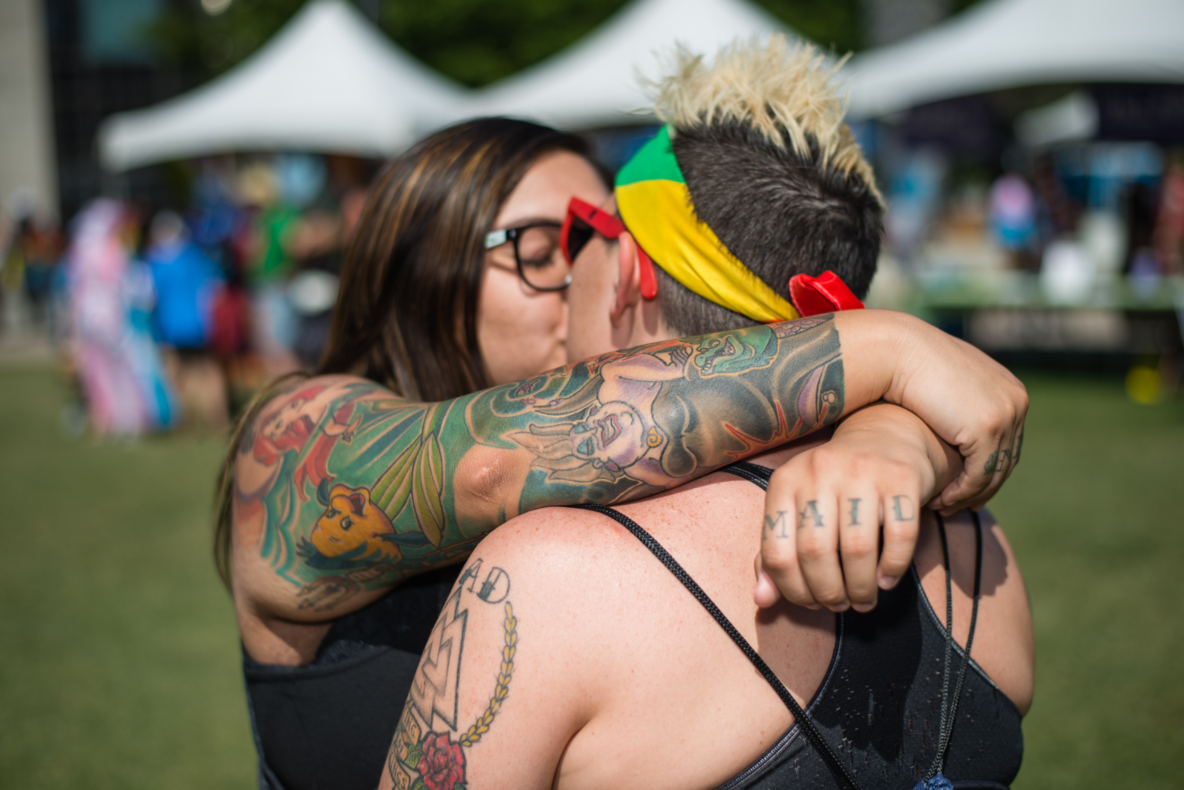 Nashville Pride Festival 2017 | Photographer + Director, Kristina Krug | authentic, authenticity, bisexual, celebrate, celebration, civil, civil liberties, courage, dancing, documentary, drag, emotions, equality, esteem, fearless, festival, festive, free, freedom, friends, fun, gay, happy, journalism, joy, joyful, Kristina Krug, krug photo, lesbian, LGBT, LGBTQ, liberty, love, love wins, loved, love is love, loveliness, lovers, love wins, men, National Pride Day, parade, people, photographer, photojournalism, photojournalist, Portrait, Predators, pride, Pride Parade, proud, queen, queer, relationship, reportage, respect, rights, safety, self, sexuality, summer, sun, sunny, Transgender, women, couple, lesbian couple with tattoos, kissing in a warm embrace at Public Square Park in Nashville, TN