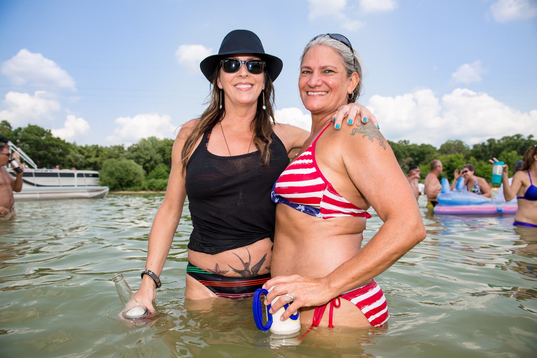Two women at a lake party, swim suit, beer, hat, coozie, real beauty, real people, boats, friends, reportage, lake party, summer fun, beverage, swimming, swim, suit, bathing, confident, summer fun, liquor, travel, Madison, Chicago, Nashville advertising,